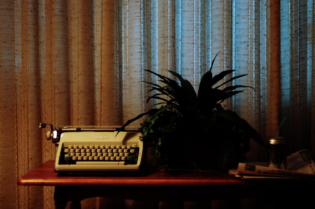 A typewriter and plant sits on a table, ready for biography writing.