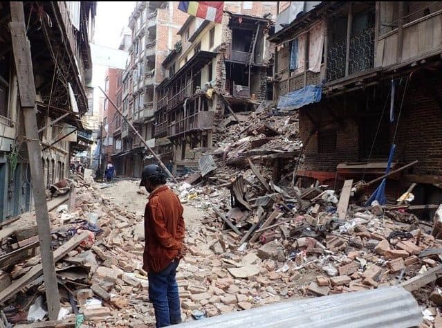 Man by collapsed building in Nepal after earthquake