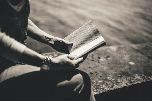 black and white image of a person reading a book